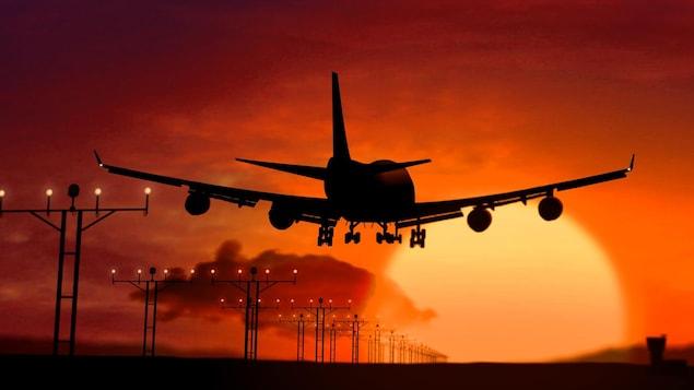 Silhouette d'avion atterrissant sur coucher de soleil.