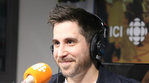 Un homme sourit devant le micro.