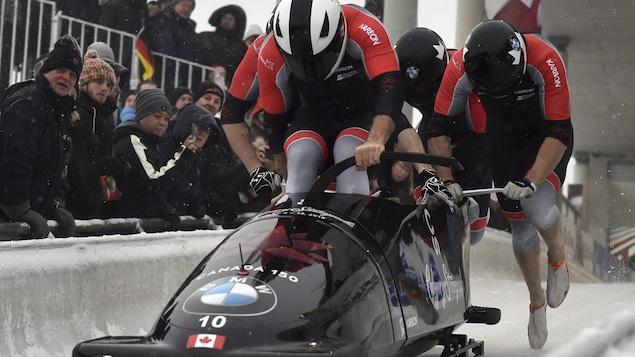 Quatre hommes qui poussent un bobsleigh lors d'une compétition