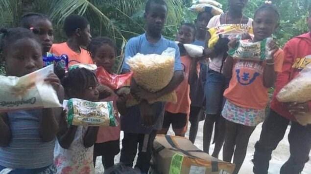 Des enfants haïtiens avec des denrées plein les mains.
