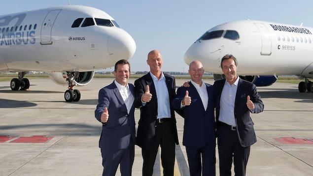 Les quatre hommes devant des avions Airbus et C Series.