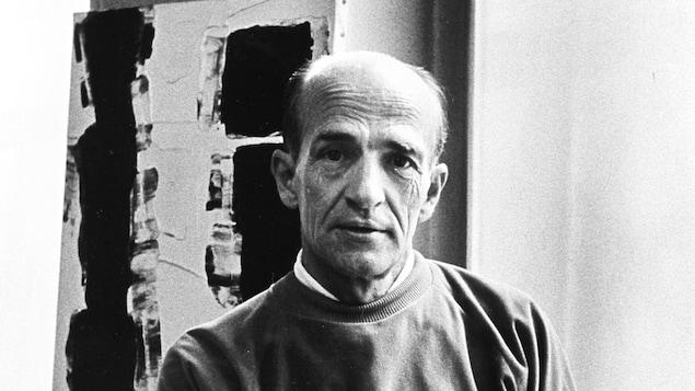 Photo en noir et blanc représentant Paul-Émile Borduas, qui pose devant une peinture