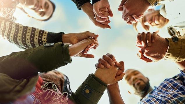 Un groupe d'amis se tiennent par la main le temps d'une prière.