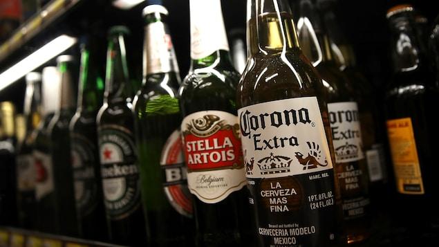 Des bouteilles de bière alignées sur une étagère.