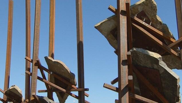 Des poutres de métal rouillé avec des plaques de pierres suspendues