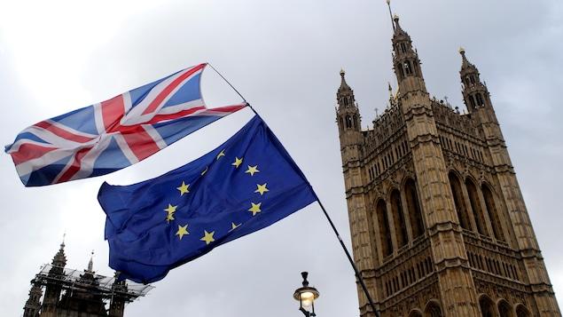 Le drapeau de l'union européenne et le drapeau britannique brandis devant la tour Big Ben.