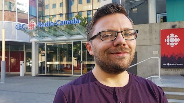 Un homme est posé plan taille devant l'immeuble de Radio-Canada.