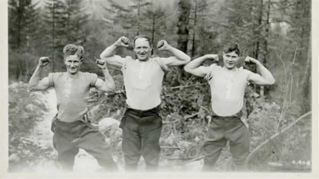 Trois bûcherons dans une photo en noir et blanc qui montrent leurs muscles de bras