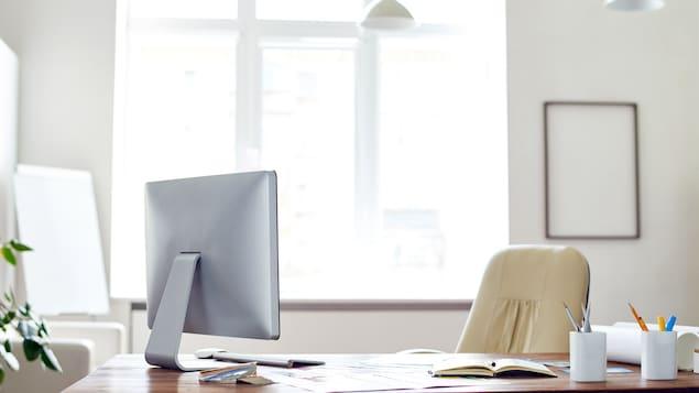 Un bureau avec un ordinateur, du papier et des fournitures et une chaise.