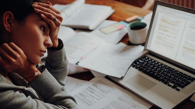 Le Mouvement Santé mentale Québec vient de regrouper dans une trousse COVID un ensemble d'outils pour aider les travailleurs qui vivent de la détresse psychologique en cette période de pandémie. Une femme assise à une table où se trouve une ordinateur portable et de nombreux documents.
