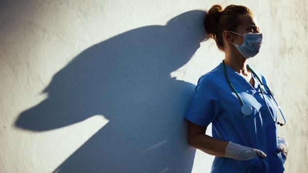 Une travailleuse de la santé adossée contre un mur qui regarde au loin.