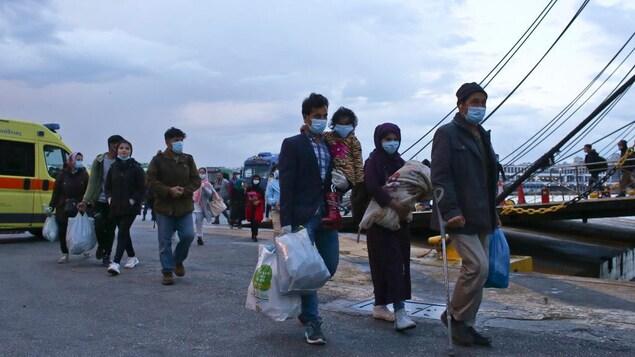 Des migrants portent des masques.