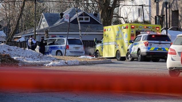 Des policiers discutent près d'une voiture de patrouille et d'une ambulance stationnées dans un rond-point.