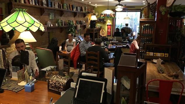 L'intérieur du café Floraison. On y voit six clients, des livres sur une tablette et une mandoline au fond.