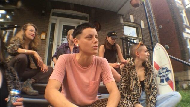 La rappeuse est entourée d'autres femmes, toutes assises sur les marches d'un balcon.