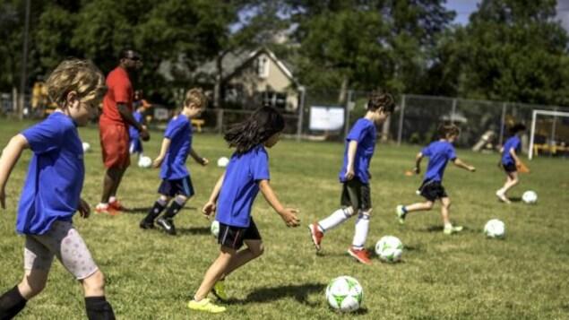 Des enfants tapent dans un ballon de soccer.