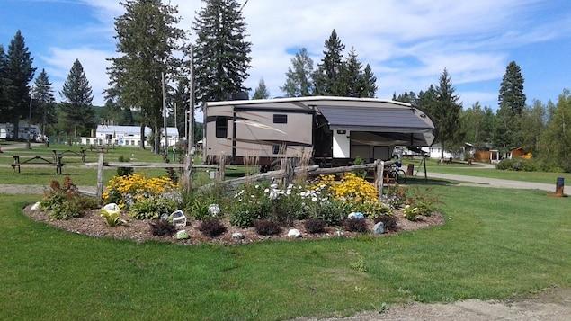 Une tente roulotte se trouve sur un terrain de camping, ainsi que des petites maisons en arrière-plan.