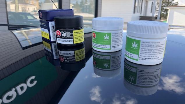 Quatre contenants de cannabis déposés sur le capot d'une voiture, devant une succursale de la SQDC.
