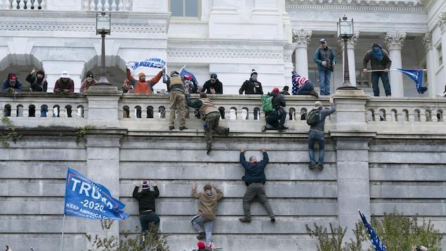 Des gens grimpent une façade en pierre autour du Capitole.