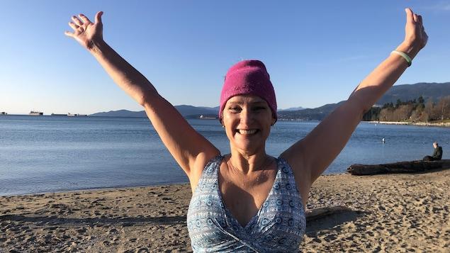 Carine Bocabeille-McEwan est trempée en maillot et sourit sur la plage.