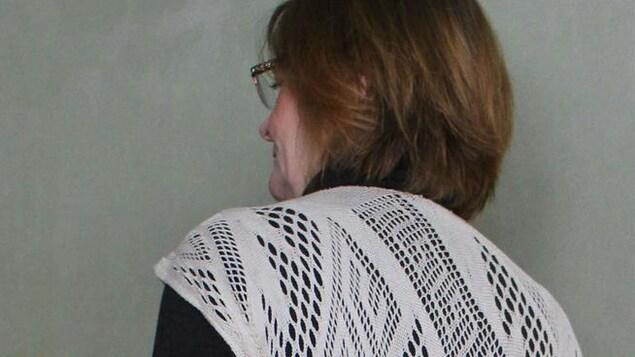 Carol James de dos, portant une tunique tissée.