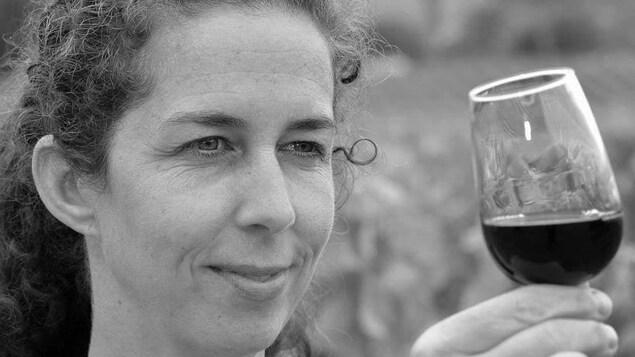 Caroline Schaller regarde un verre de vin rouge.