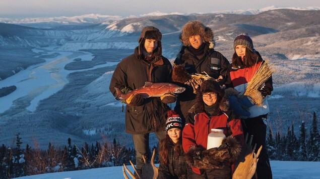 Les 5 membres 'dune famille posent en haut d'une montagne au Yukon.