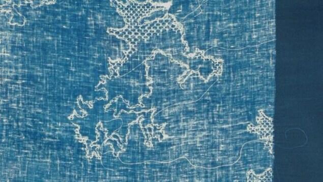 une oeuvre abstraite faite de fil, de papier, sur fond bleu.