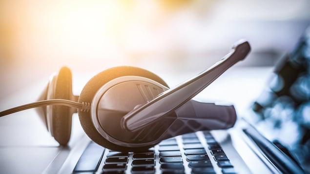 Des écouteurs munis d'un micro posés sur le clavier d'un ordinateur.