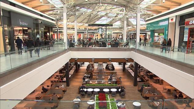 Des gens circulent dans un centre commercial à deux étages. En bas, on voit une série de tables et des arrangements floraux, tandis qu'en haut, un café Starbucks trône au centre des différentes boutiques.