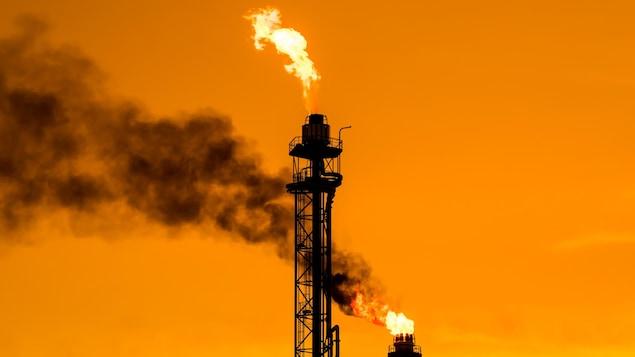 Des flammes brûlent au sommet de deux cheminées, dans une raffinerie de pétrole.
