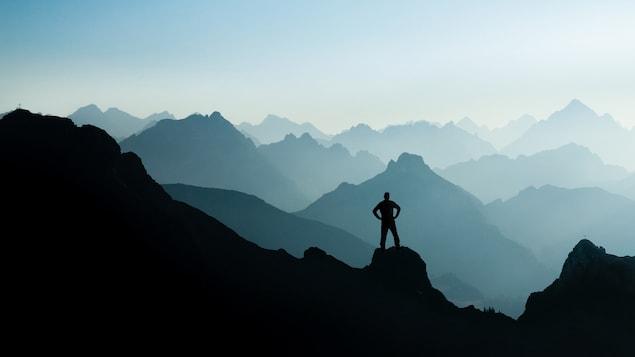 Un homme contemple des sommets dans la brume.