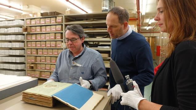 Mario Robert, Jean-François Nadeau et Annie Desrochers regardent un livre épais et ancien ouvert devant eux.