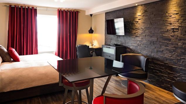 Chambre d'hôtel avec lit, rideau rouge, table, chaises et mur de pierre.