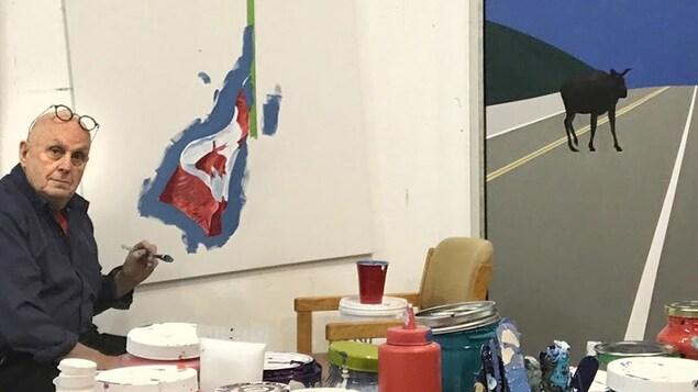 Le peintre Charles Pachter dans son atelier devant une toile en cours d'exécution
