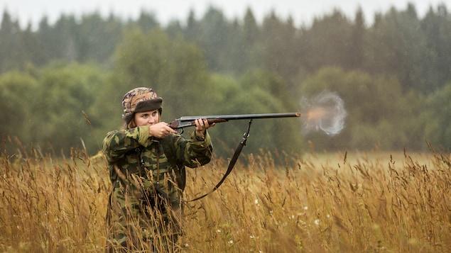 Une femme habillée en tenue de camouflage tire un coup de sa carabine.