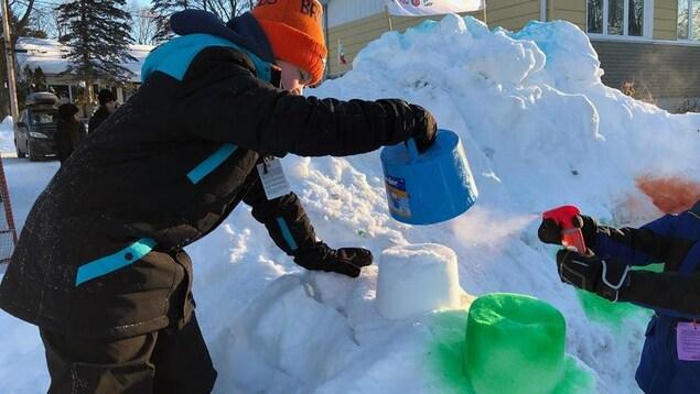 Un jeune garçon joue dans la neige avec un récipient bleu