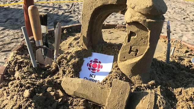 Un château de sable en forme de micro avec le logo de Radio-Canada