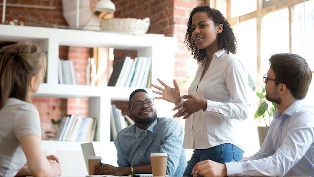 Une femme noire parle debout autour d'une table à deux hommes et une femme.