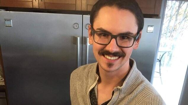 Un homme souriant présente un plateau de viande variées d'une main.
