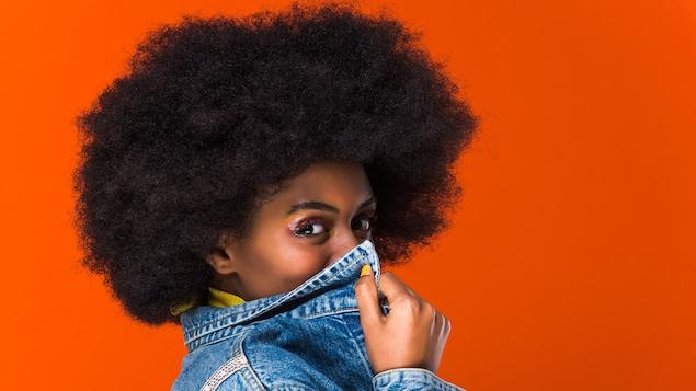Une femme noire aux cheveux frisés se cache une partie du visage avec son manteau de jeans.
