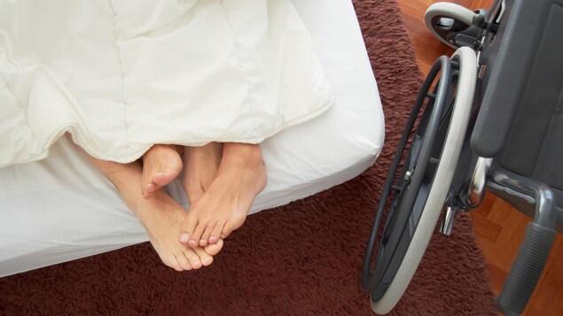 On voit quatre pieds emmêlés dans un lit et une chaise roulante à côté.