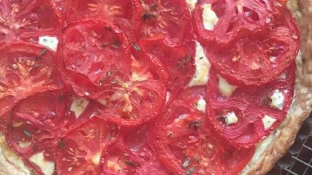 Une tarte à la tomate est déposée sur une grille.