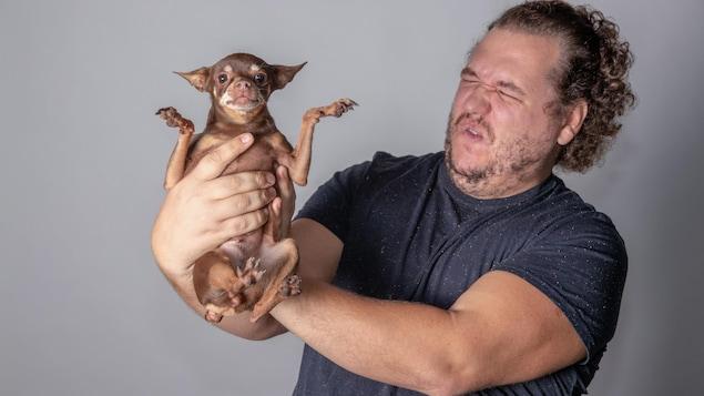 Un homme a une moue de dégoût en tenant un petit chien au bout de ses bras.