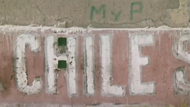 Partie d'une murale dans un quartier populaire de Santiago au Chili avec le nom du pays écrit en espagnol.