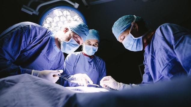 Des chirurgiens en bleu autour d'une table d'opération.