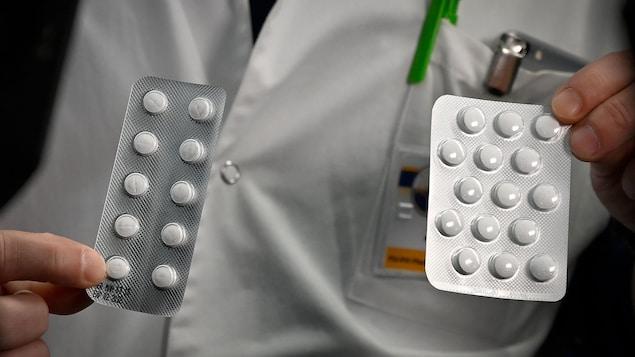 Un homme en sarrau tient deux plaquettes de comprimés