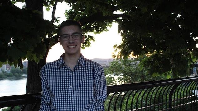 Une jeune homme devant une clôture et des arbres près d'un cours d'eau.