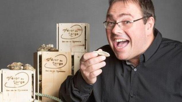 Christian Vigneau, propriétaire de l'entreprise Les Cultures du Large aux Îles-de-la-Madeleine, s'apprêtant à manger une huître.