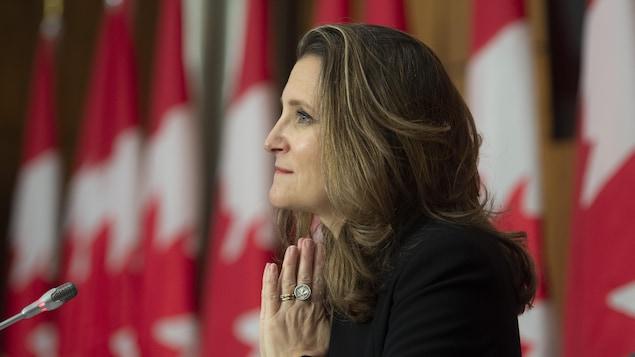 Chrystia Freeland, les mains jointes comme si elle priait, lors d'une conférence de presse, avec des drapeaux canadiens en arrière-plan.